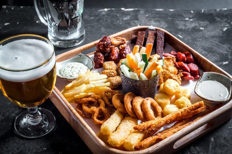 Комплект сортированных закусок пива - сосисок, крылов цыпленка, гренков, колец лука и колец кальмара на деревянной доске с соусом стоковая фотография rf