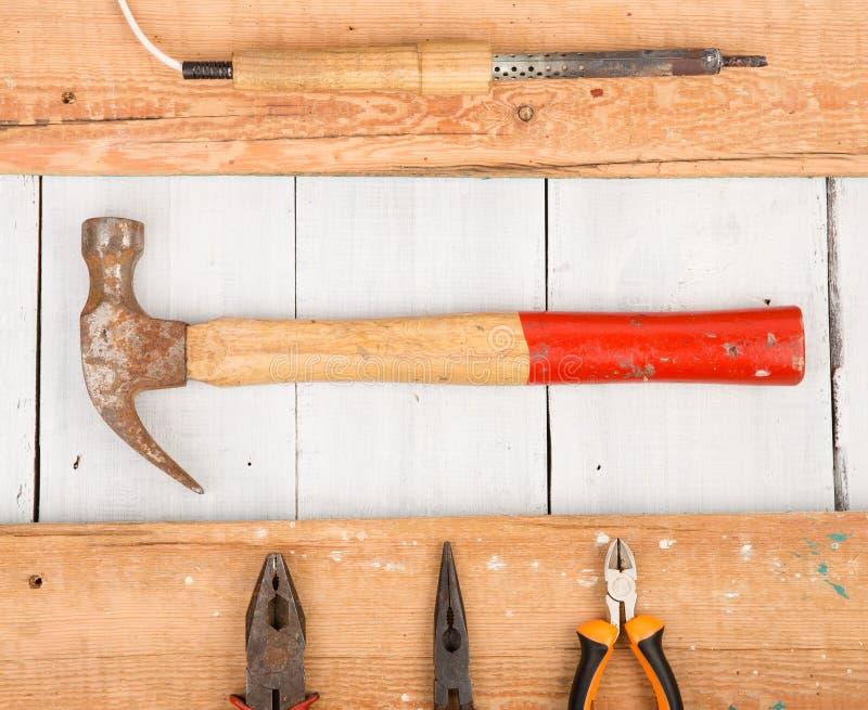 Комплект старых инструментов - молотка, плоскогубцев и паяя утюга на деревянном b стоковое изображение rf