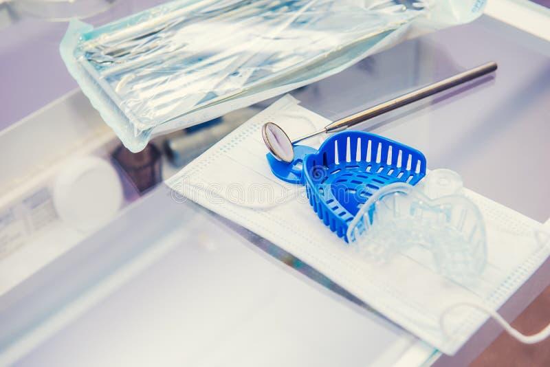 Комплект упакованных простерилизованных инструментов медицинского оборудования, mirrow ` s дантиста и прессформ челюсти на маске  стоковые изображения