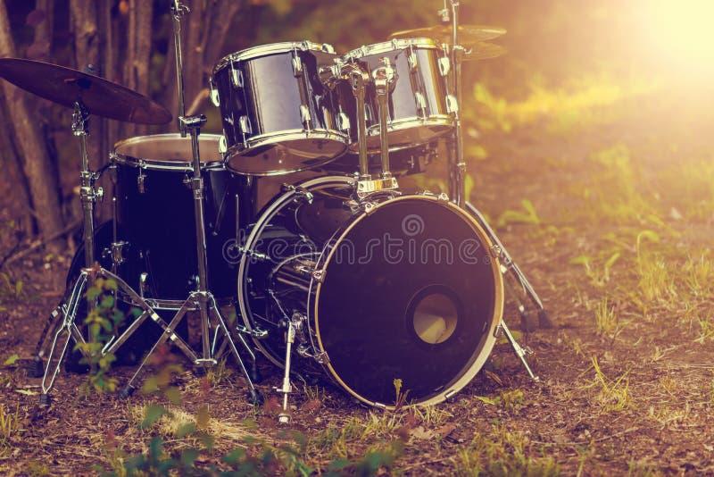 Комплект черного барабанчика батареи установил под дерево на траве Винтажный тон стоковые фото
