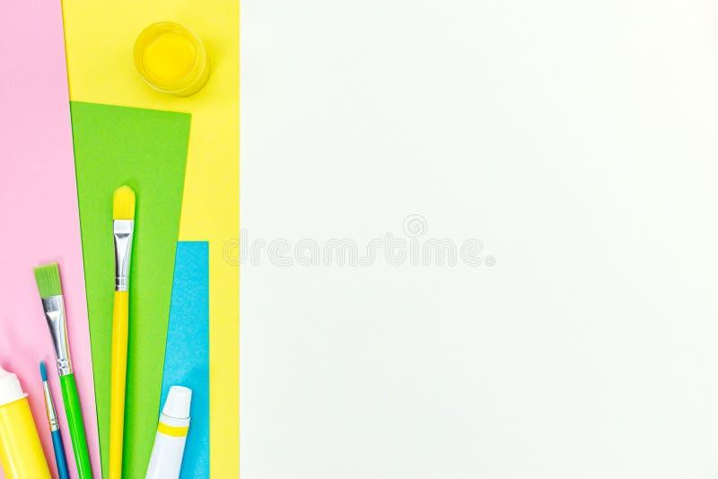 Комплект щеток, красок и покрашенной бумаги альбома на белом bac стола стоковое фото