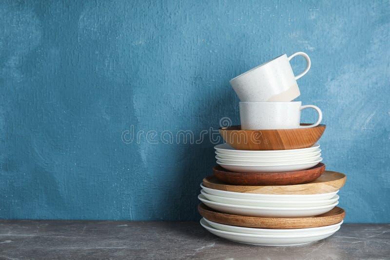 Комплект dinnerware на таблице против предпосылки цвета с космосом для текста стоковая фотография rf