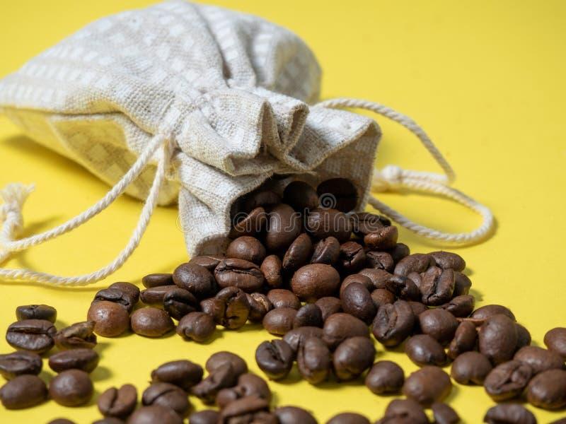 Композиция с кофе кофейные зерна выливаются из мешка на фоне стоковые фотографии rf