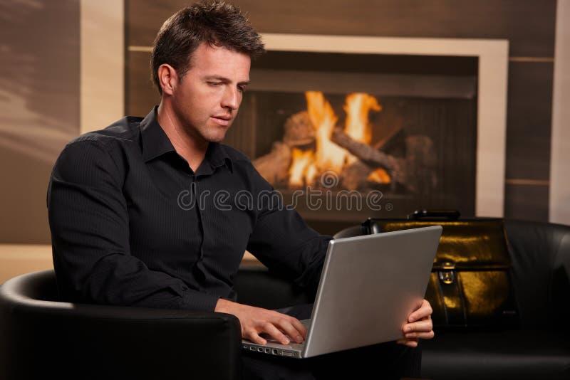 компьтер-книжка бизнесмена вскользь домашняя используя стоковое фото rf