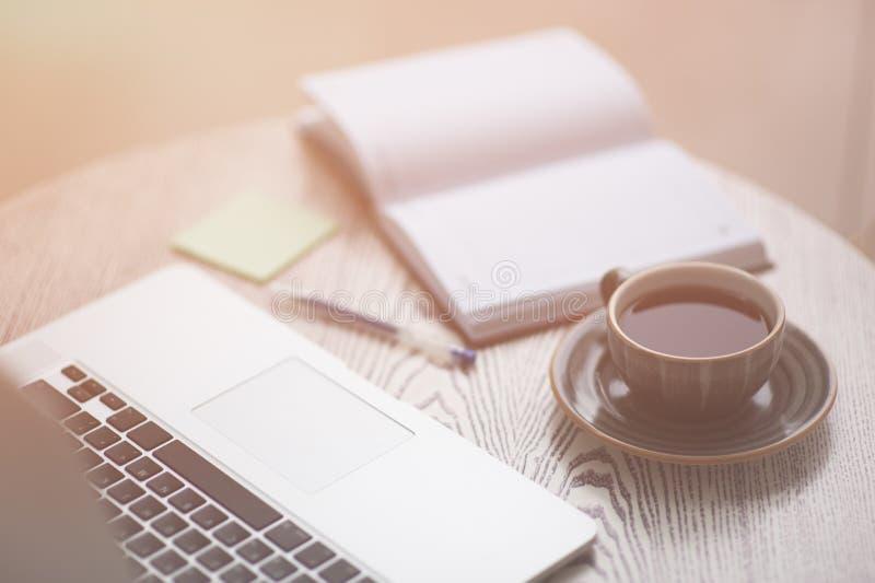 Компьтер-книжка, блокнот, ручка и чашка чаю образа жизни состава на деревянном столе осветили с теплым светом стоковые фотографии rf