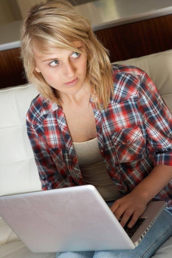 компьтер-книжка девушки виновная смотря подростковое использование стоковые фото