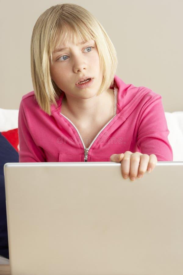компьтер-книжка девушки смотря используя потревожено стоковое фото