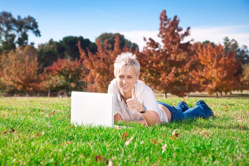 компьтер-книжка девушки outdoors сь использующ стоковое фото rf