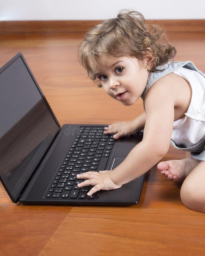 компьтер-книжка девушки компьютера младенца используя стоковая фотография rf