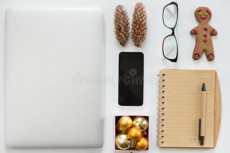 Компьтер-книжка закрыла, мобильный телефон, канцелярские товар и украшение рождества стоковая фотография rf