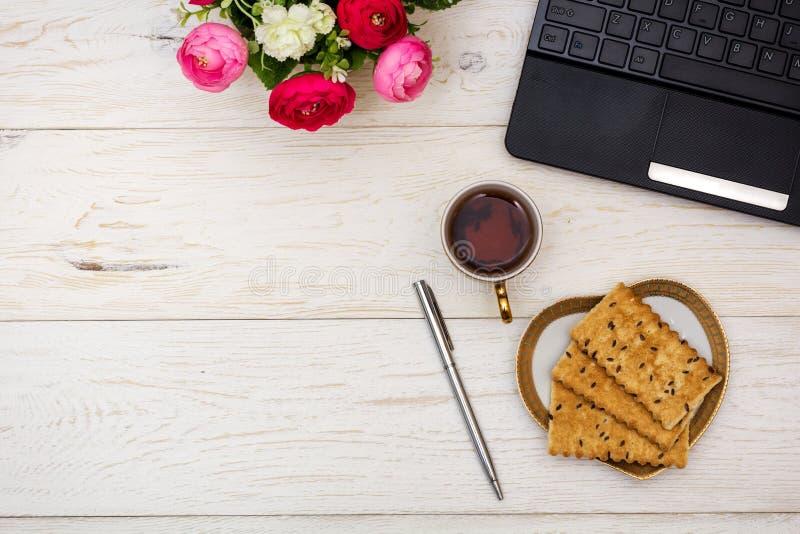 Компьтер-книжка и чашка чаю на белых досках стоковое изображение