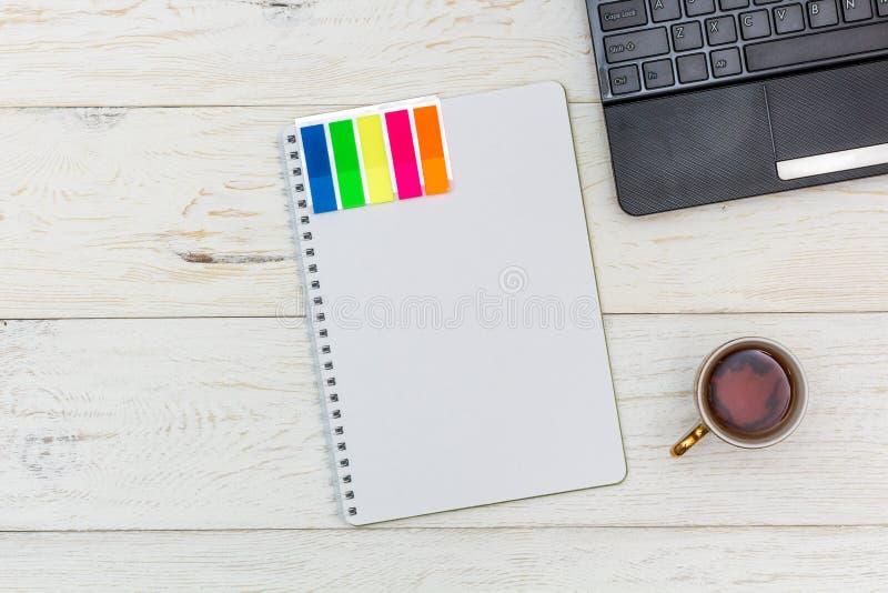 Компьтер-книжка и чашка чаю на белых досках стоковые изображения rf