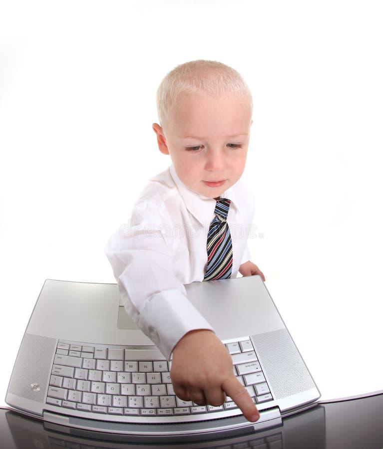 компьтер-книжка компьютера мальчика меньшяя деятельность костюма стоковая фотография