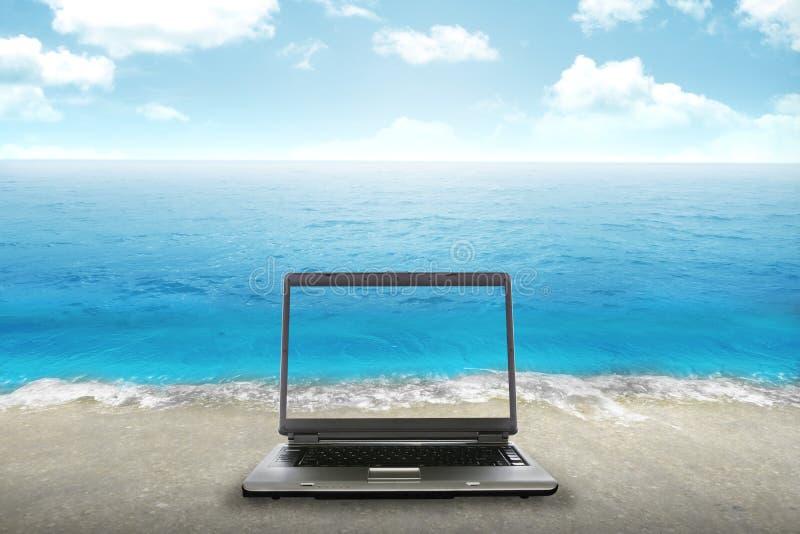 Компьтер-книжка компьютера на пляже стоковые изображения rf