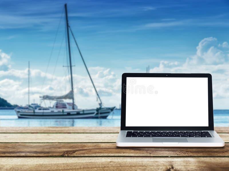 Компьтер-книжка компьютера с пустым белым экраном на деревянном столе стоковые изображения