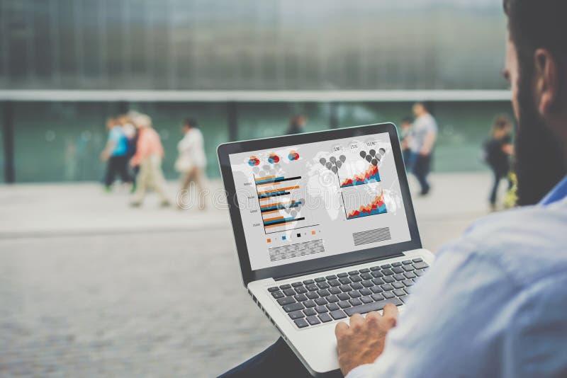 Компьтер-книжка конца-вверх с диаграммами, диаграммами и диаграммами на экране в руках бизнесмена сидя outdoors и работая стоковые изображения rf