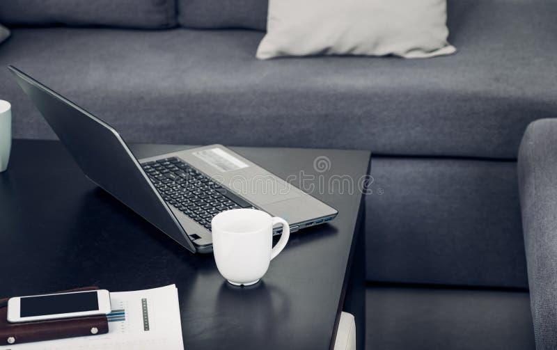 Компьтер-книжка, кофейная чашка, мобильный телефон, организатор, диаграмма дела на столе на софе в офисе, работая образ жизни стоковые фото