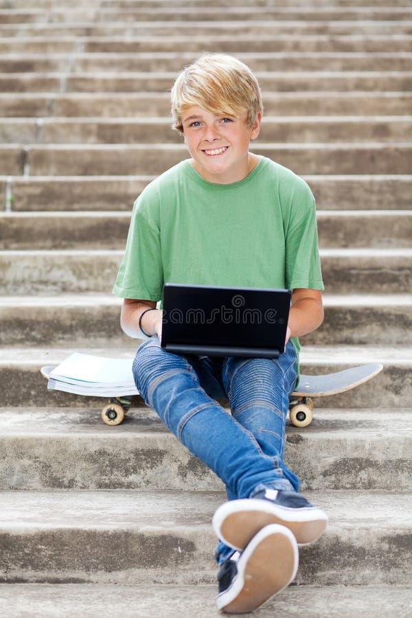 компьтер-книжка мальчика предназначенная для подростков стоковые фото