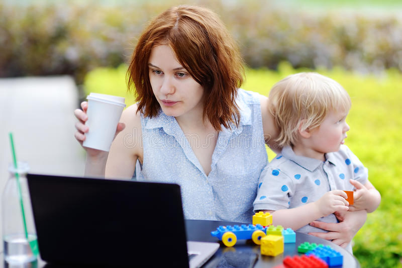 Компьтер-книжка молодой матери работая oh и держать ее сына стоковые фотографии rf