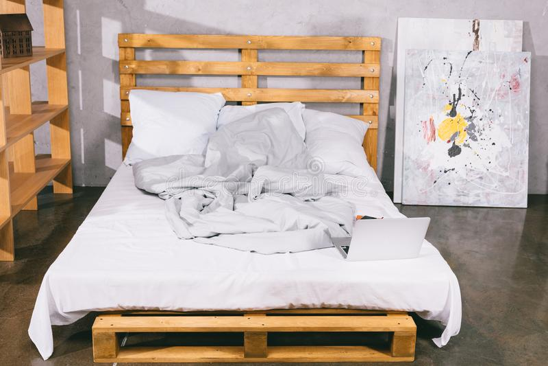 компьтер-книжка на кровати от деревянных паллетов стоковое изображение