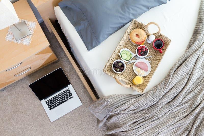 Компьтер-книжка на поле около кровати с подносом завтрака стоковые фотографии rf