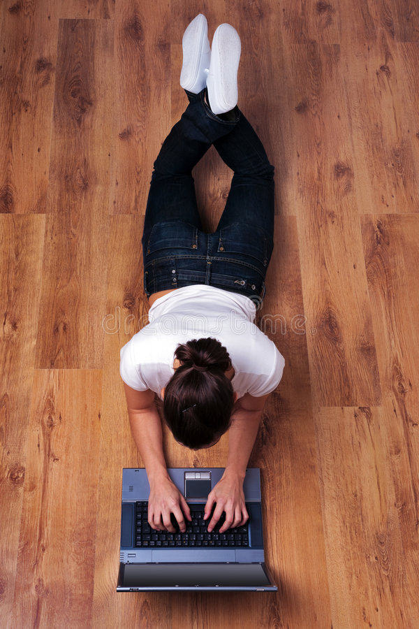 компьтер-книжка пола лежа используя женщину деревянную стоковое изображение rf