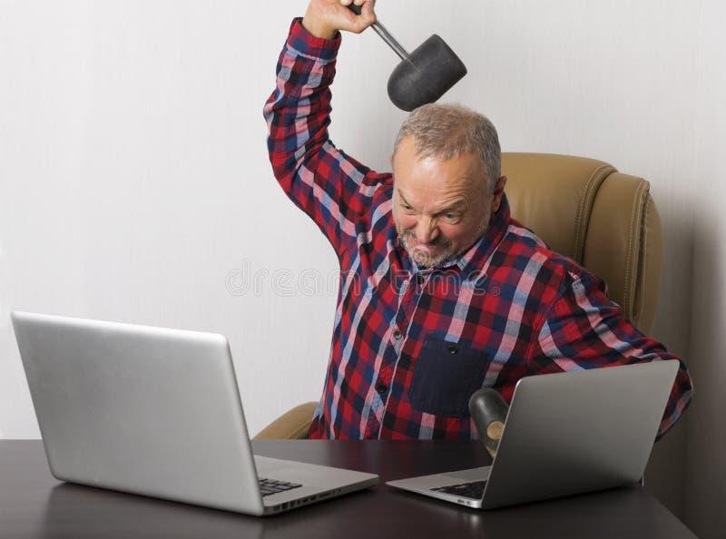 Компьтер-книжка сердитого человека разбивая стоковое фото rf