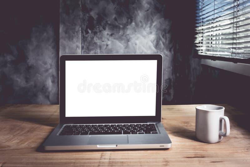 Компьтер-книжка с белыми пустым экраном и чашкой кофе на деревянном столе с предпосылкой стены grunge стоковое изображение rf