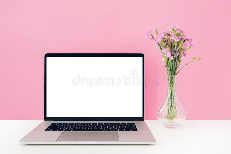 Компьтер-книжка с белыми пустым экраном и цветками в вазе на таблице на розовой предпосылке Насмешка вверх стоковое изображение