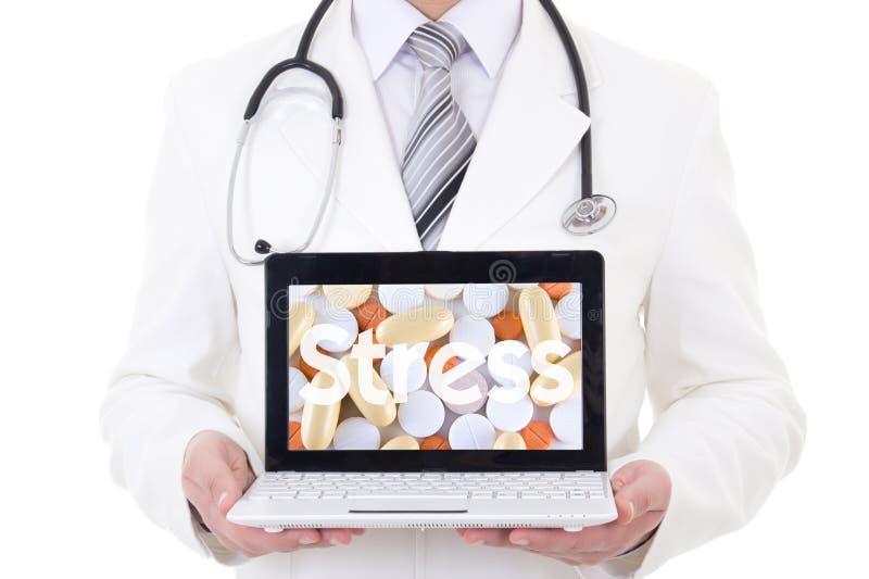 Компьтер-книжка с таблетками и стресс слова в руках доктора стоковые фото