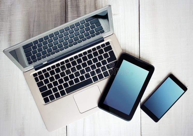 Компьтер-книжка таблетки телефона электронных устройств цифров на древесине стоковые изображения