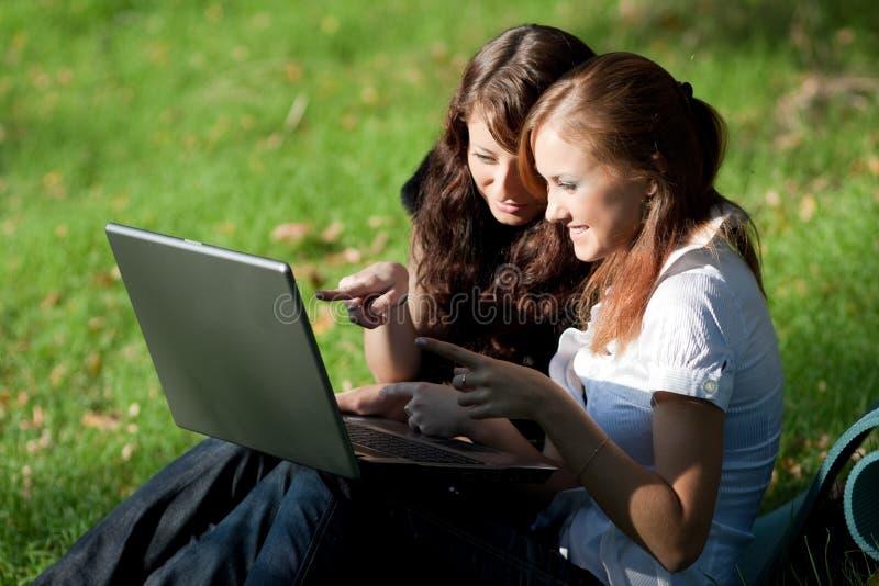 компьтер-книжка 2 девушок стоковое фото
