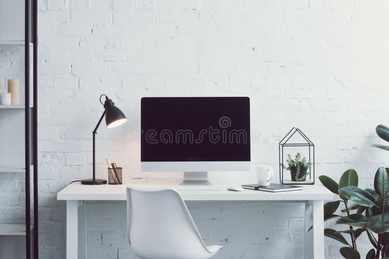 компьютер, белая таблица, стул и заводы в современном рабочем месте стоковое изображение