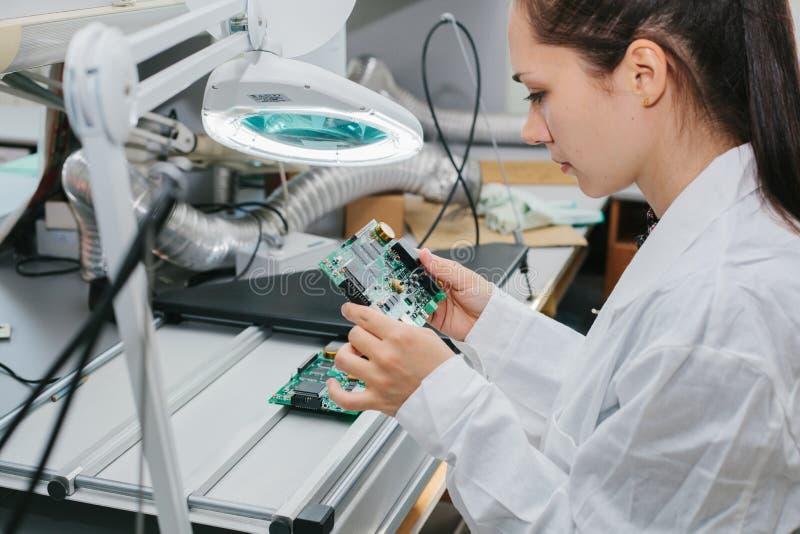 Компьютер доски красивого женского техника компьютерного эксперта профессионального рассматривая в лаборатории в фабрике стоковые фотографии rf