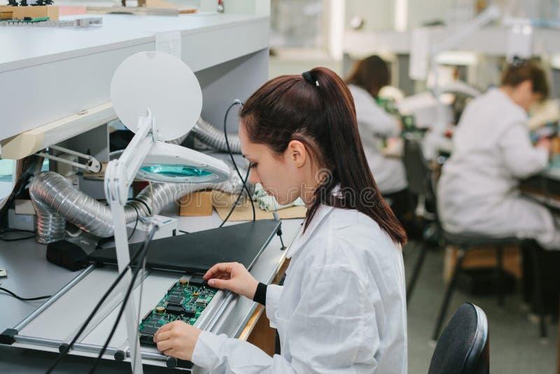 Компьютер доски красивого женского техника компьютерного эксперта профессионального рассматривая в лаборатории в фабрике стоковые изображения