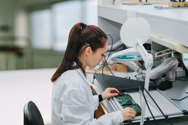 Компьютер доски красивого женского техника компьютерного эксперта профессионального рассматривая в лаборатории в фабрике стоковое фото rf
