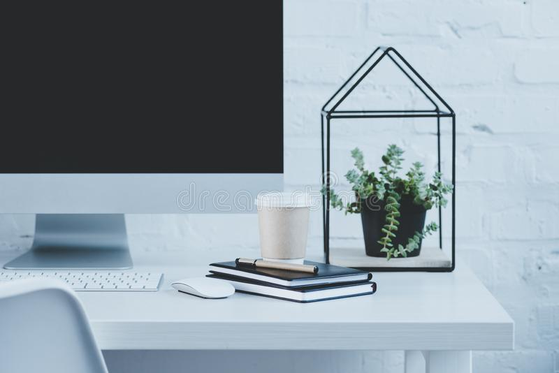 компьютер и устранимая кофейная чашка на таблице в современном рабочем месте стоковые фотографии rf