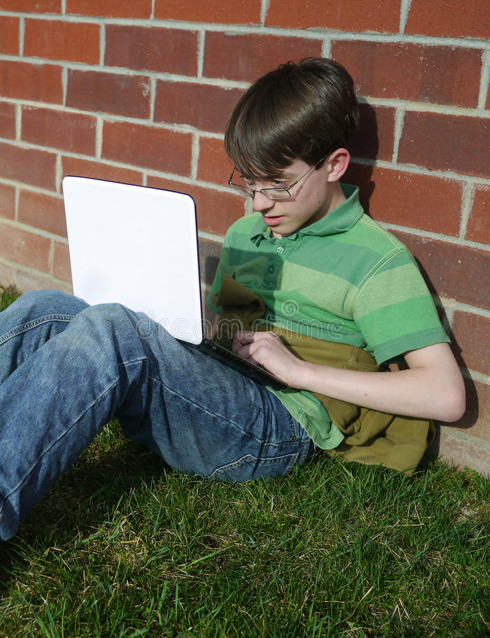 компьютер мальчика вне школы используя стоковое изображение rf
