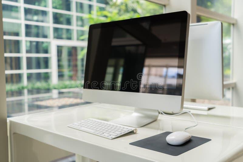 Компьютер на таблице в офисе, месте для работы стоковые изображения