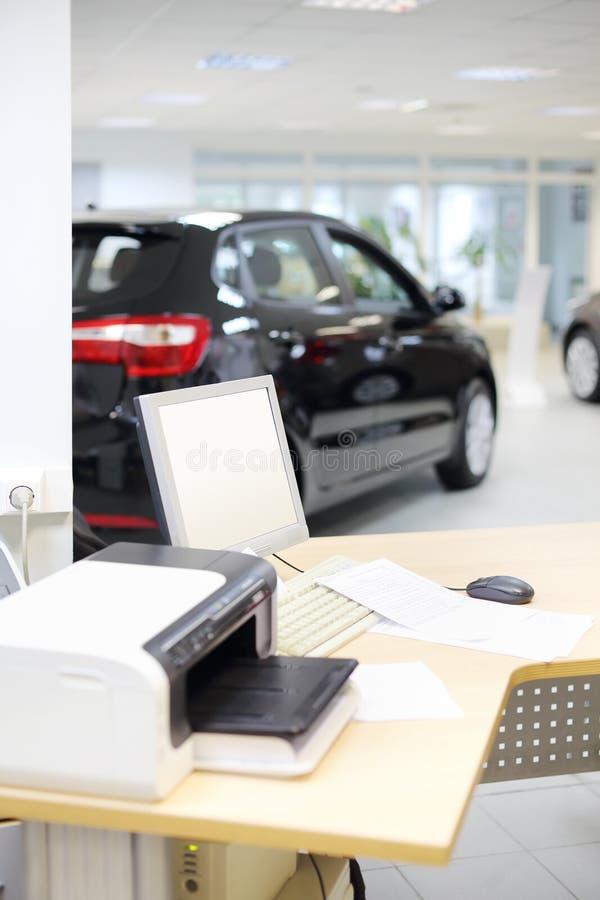 Компьютер, принтер и документы на деревянном столе и новом автомобиле стоковая фотография rf