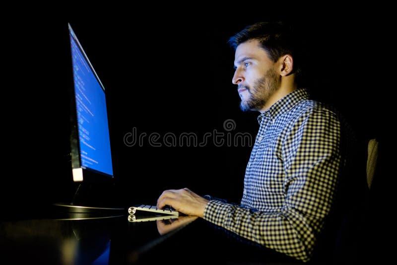 Компьютер разработчика программного обеспечения на темном домашнем офисе стоковые изображения rf