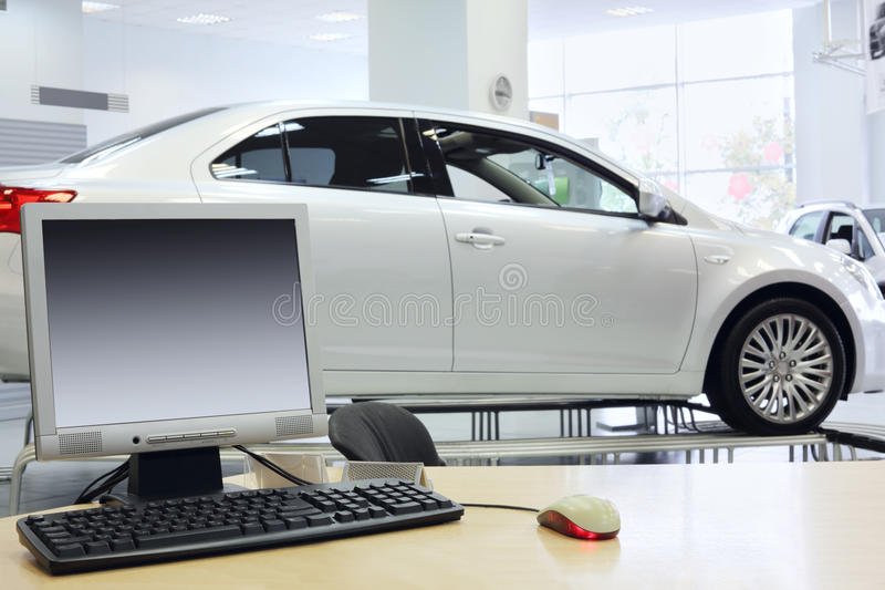 Компьютер стоит на таблице и новом белом автомобиле стоковые фото