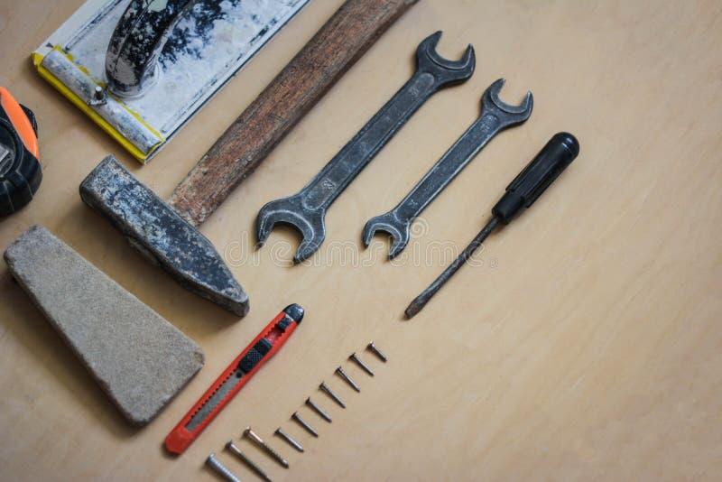 Комплект аппаратур для ремонтировать на деревянном взгляд сверху стоковые фото