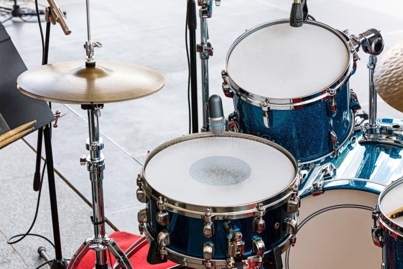 Комплект барабанчиков, цимбал и микрофонов на предпосылке мостоваой стоковые изображения