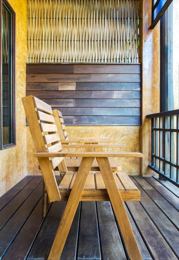 Комплект деревянного стола и стула с абстрактной стеной на винтажном балконе стиля садом стоковые изображения