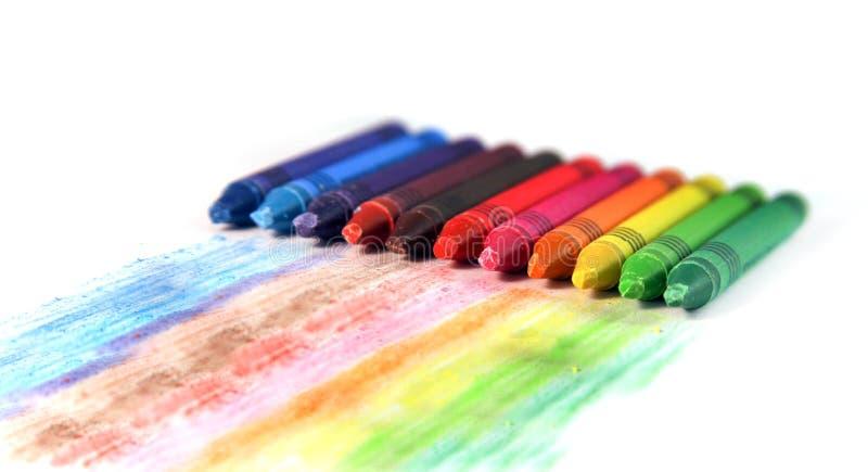 Комплект пестротканых crayons воска с нашивками чертежа на белизне стоковое изображение rf