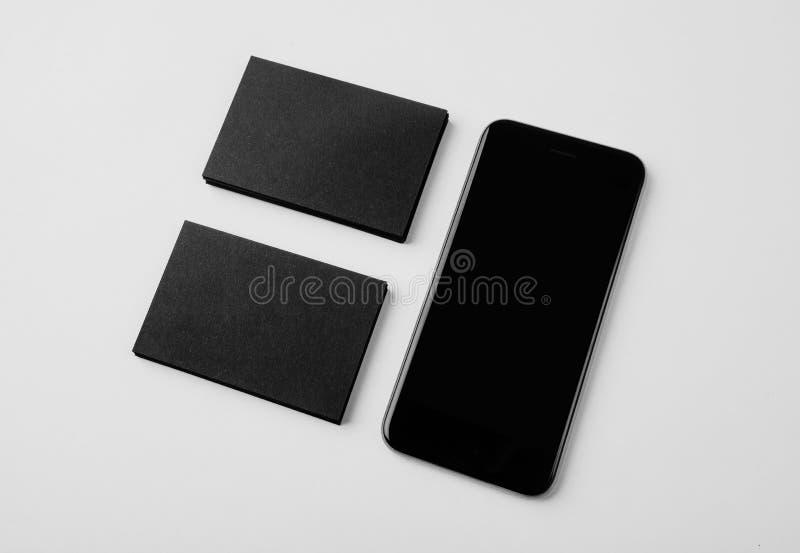 Комплект пустых черных визитных карточек и smartphone на белой предпосылке горизонтально стоковое фото rf