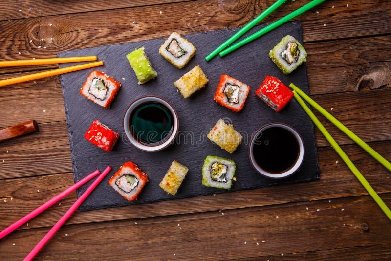 Комплект суш свертывает при служат соевый соус, который на сером каменном шифере стоковые фотографии rf