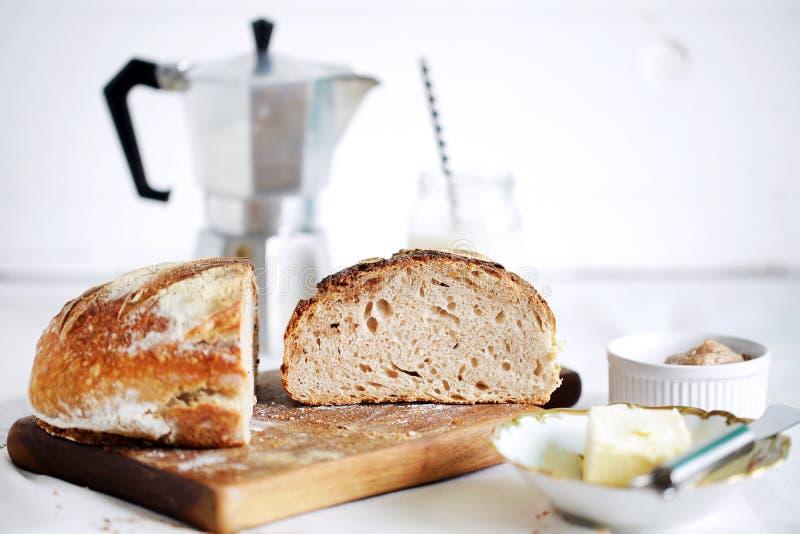 Комплект таблицы завтрака с хлебом, маслом и кофе sourdough отрезка деревенским стоковая фотография rf