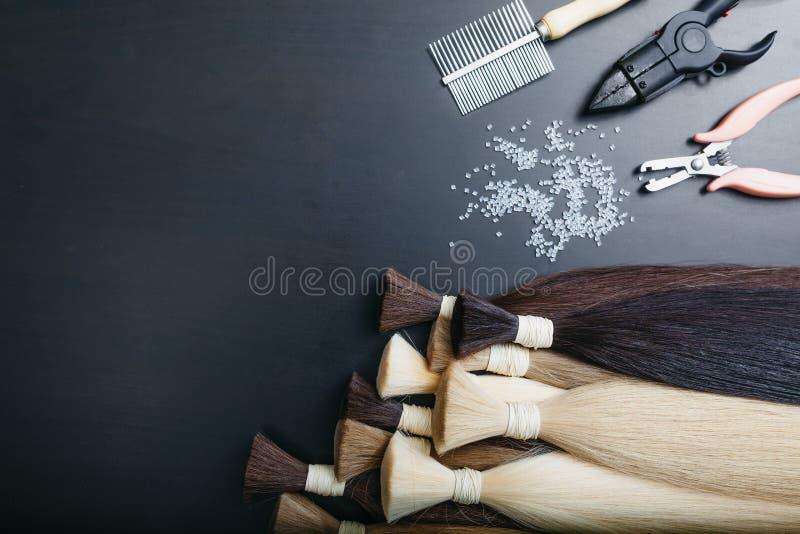 Комплект sevral инструментов расширения волос цвета на темной предпосылке стоковое фото rf
